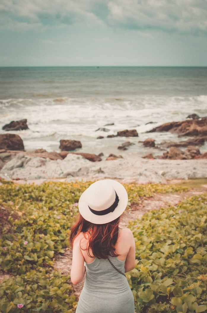 selective focus photography of woman wear white fedora hat standing on green plant watching sea