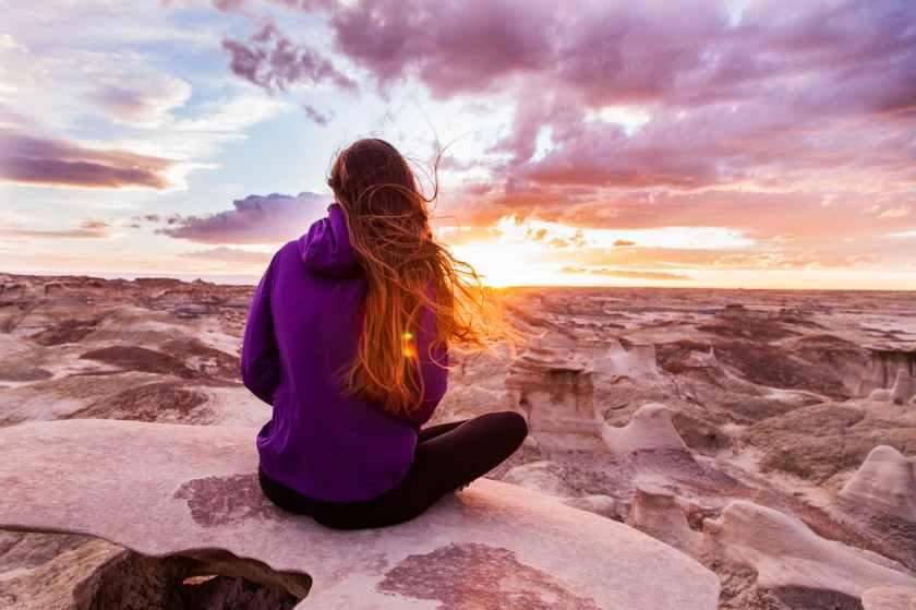 woman wearing purple hooded jacket sitting on rock