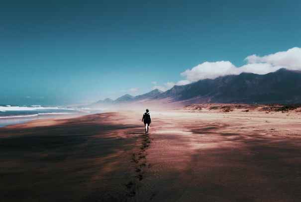 photo of person walking on deserted island