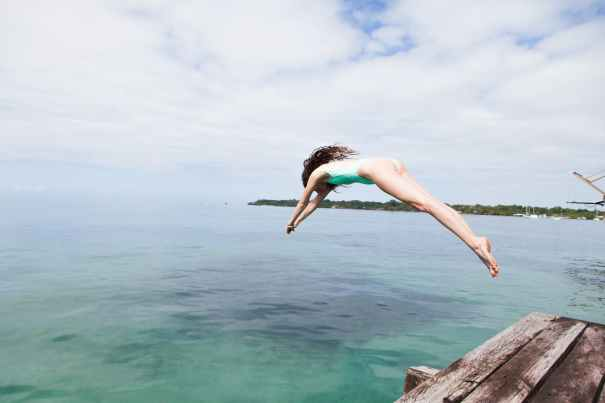 photo of woman diving into the water