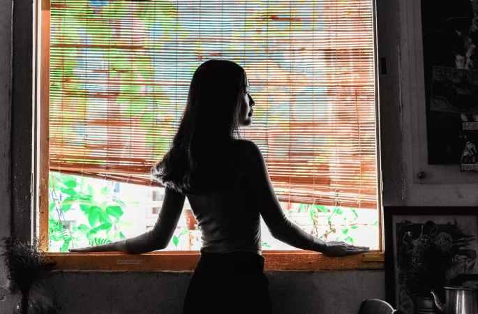 woman looking outside window